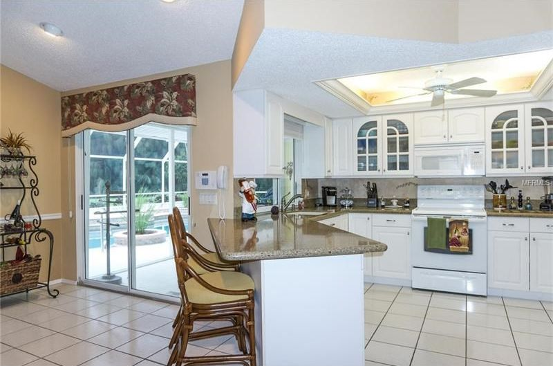 Traditional kitchen with limestone tile floors ceiling for Kitchen cabinets venice fl