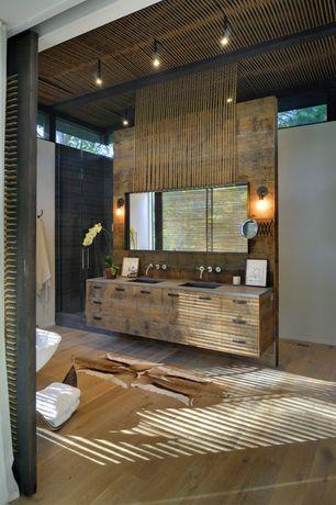 Tropical Master Bathroom With Hardwood Floors, Wall Sconce, Double Sink,  Freestanding Bathtub,