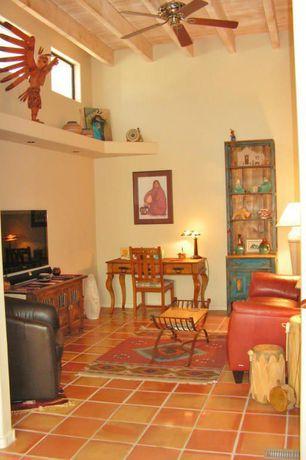 Rustic Living Room with Exposed beam, Ceiling fan, terracotta tile floors,  Built-