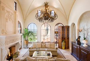 Mediterranean Living Room With Crown Molding, Chandelier, Arched Window,  Sandstone Tile Floors,