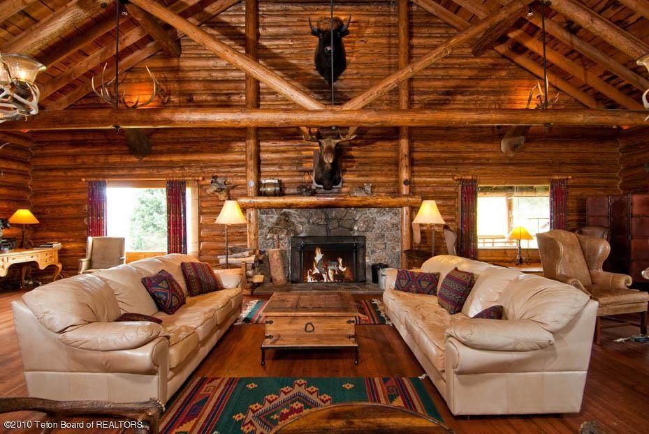 Rustic Living Room With Hardwood Floors Cathedral Ceiling Carpet Chandelier Stone Fireplace