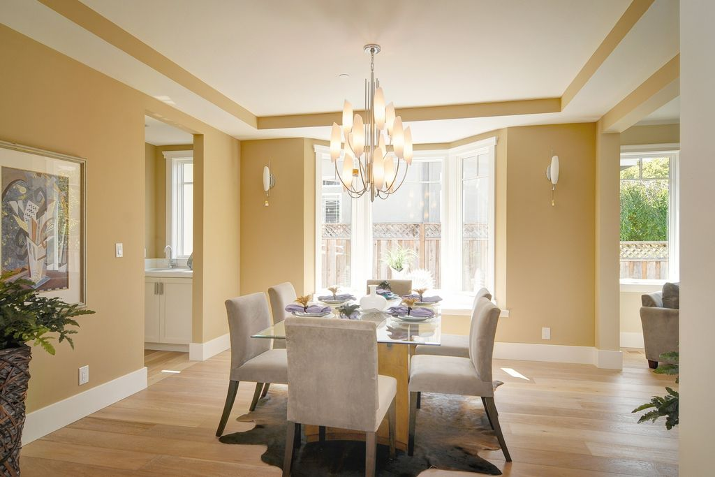 Modern Dining Room With Hardwood Floors, Chandelier, Wall Sconce, Window  Seat, High