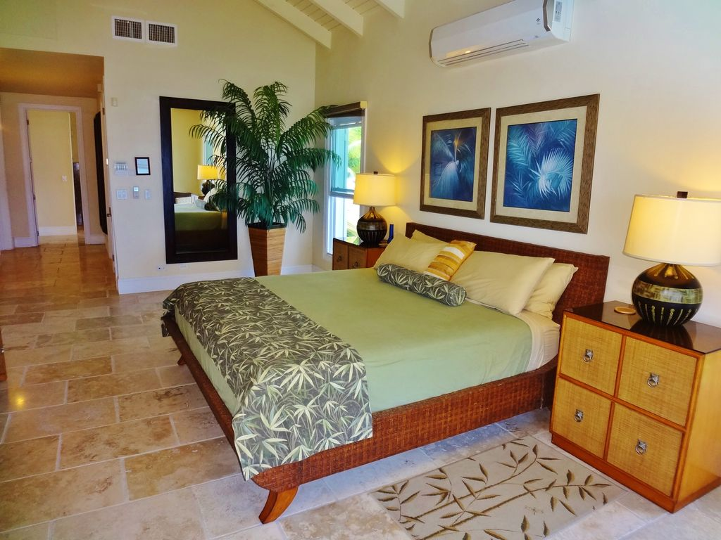 tropical master bedroom with travertine tile floors & high ceiling