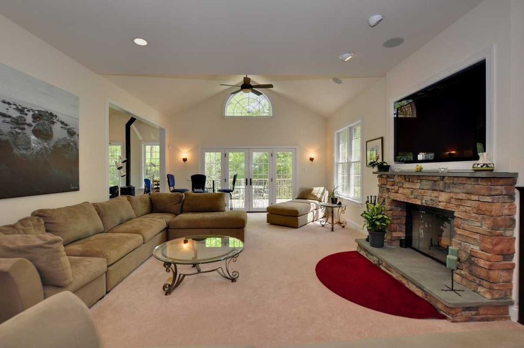 contemporary family room with high ceiling stone fireplace ceiling fan carpet flush
