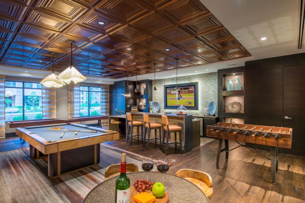 Modern Game Room with High ceiling, Built-in bookshelf, Carpet, Pendant  Light