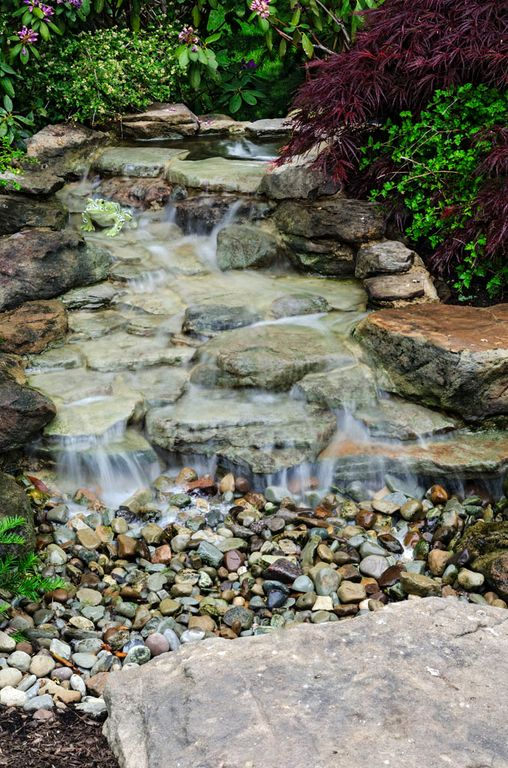 Contemporary landscape and yard with exterior stone floors for Modern pond waterfall