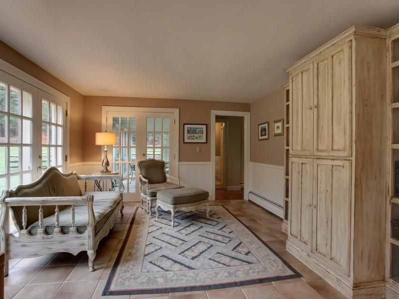 Cottage Living Room With Wainscoting French Doors Travertine Tile Floors Built In