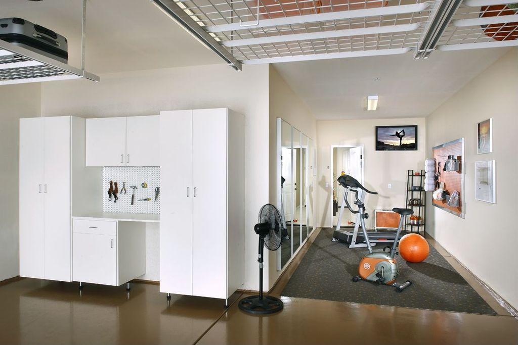 Contemporary home gym with concrete floors exposed beam