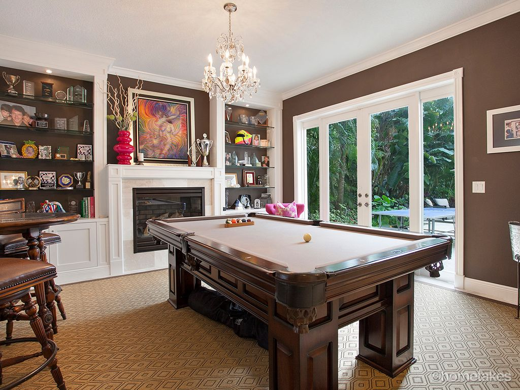 traditional game room with built in bookshelf high ceiling crown molding carpet