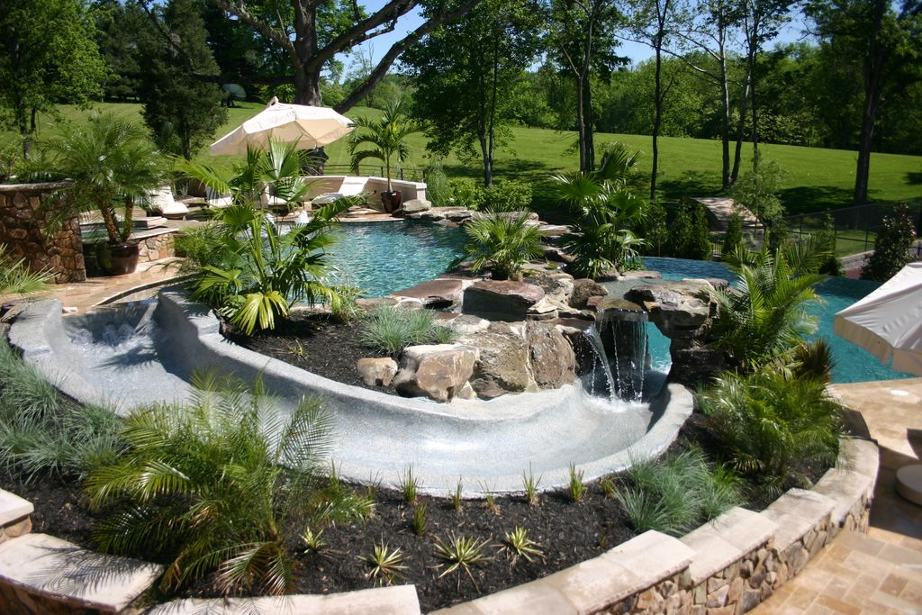 Pool Beds tropical swimming pool with exterior stone floors & raised beds