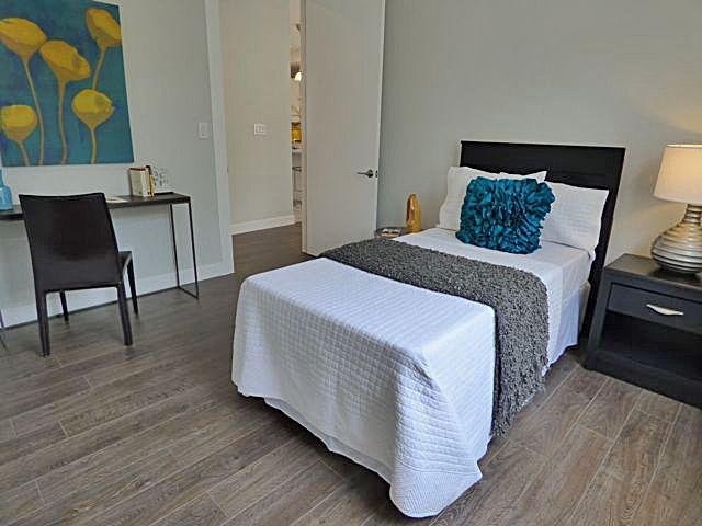 Modern Guest Bedroom with Hardwood floors by Annie PinskerBrown