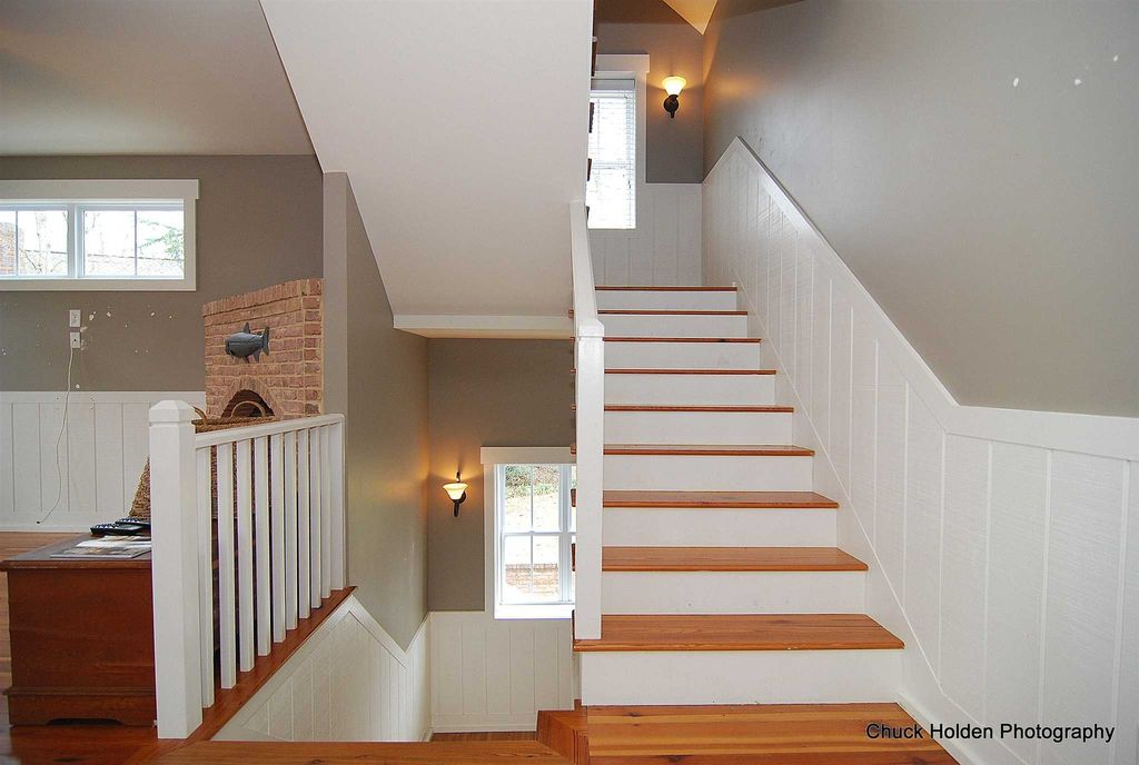 Craftsman Staircase With Wall Sconce, High Ceiling, Wainscoting, Carpet