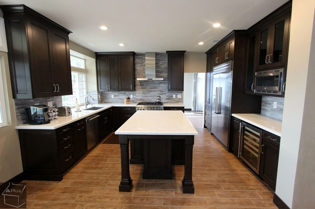 Kitchen with dark stained cabinets by aplus interior for Kitchen design zillow
