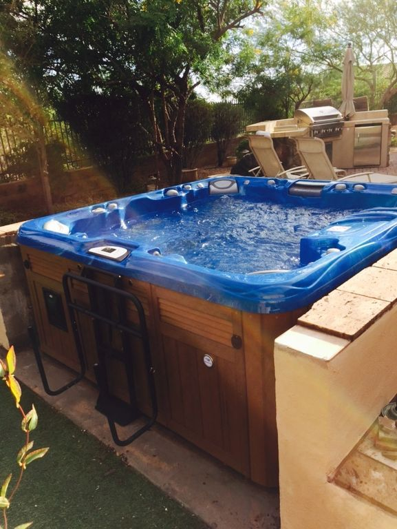 traditional hot tub with fence outdoor kitchen exterior stone floors