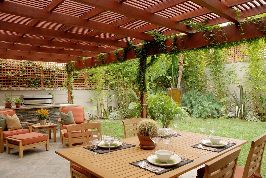 Contemporary Patio With Exterior Stone Floors, Outdoor Kitchen, Trellis,  Fence
