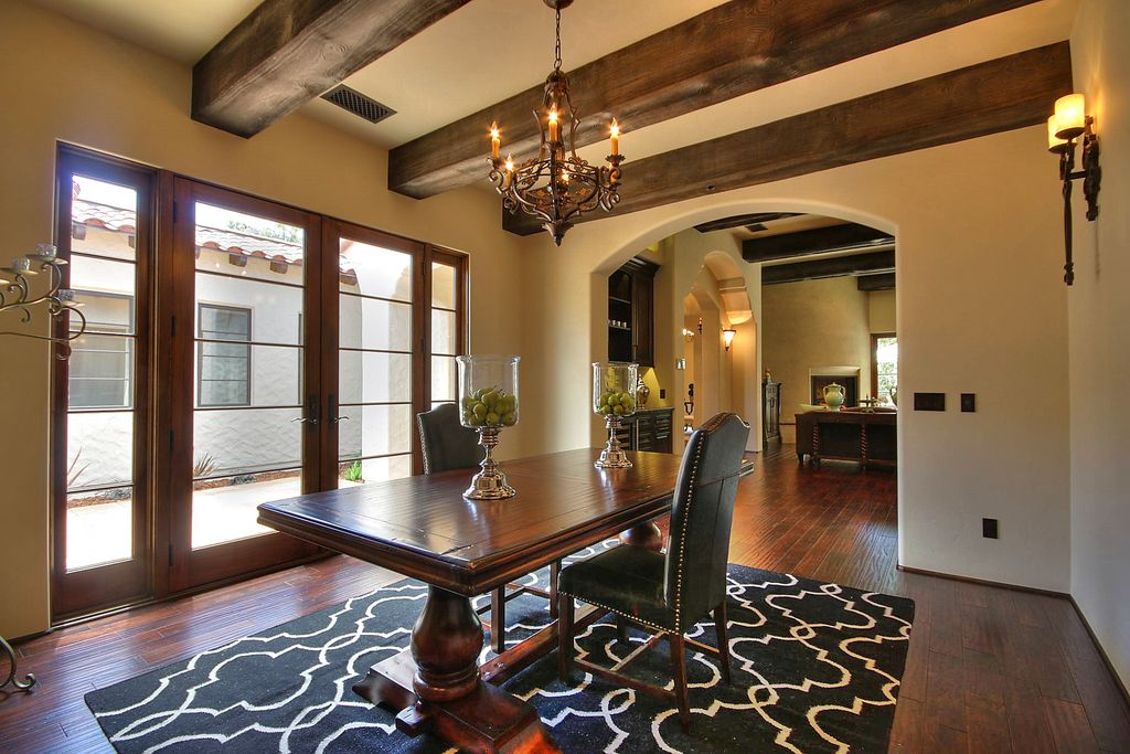 Mediterranean Dining Room With Hardwood Floors French Doors Chandelier Exposed Beam Wall