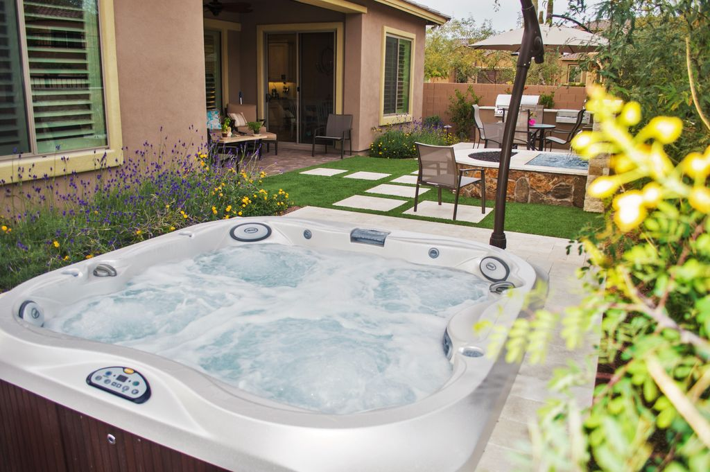 traditional hot tub with pathway fountain fence fire pit outdoor kitchen