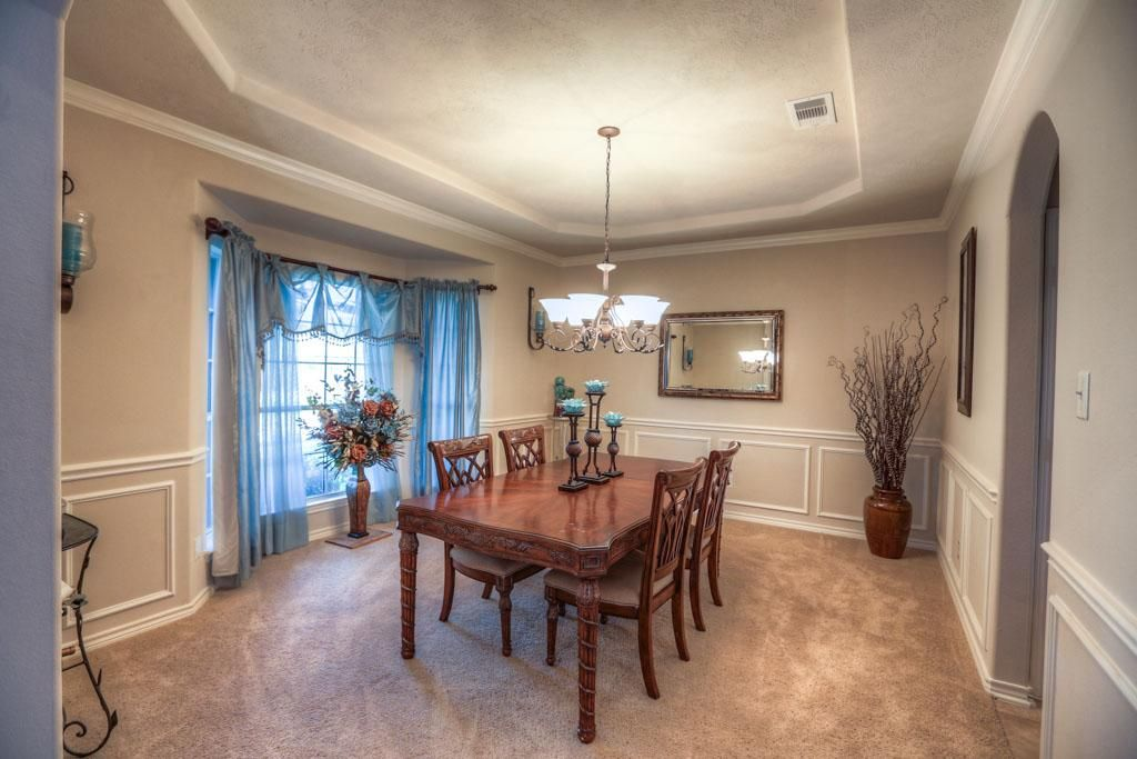 Traditional Dining Room With Carpet Crown Molding Wainscoting Bay Window Chandelier