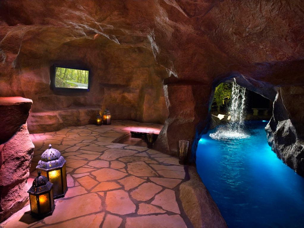 Inside Pool Cave rustic swimming pool with water feature & indoor pool | zillow
