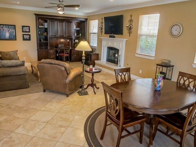 Traditional Dining Room With Crown Molding, Cement Fireplace, Ceiling Fan,  Travertine Tile Floors