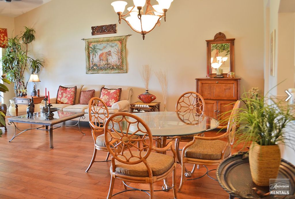 Tropical Dining Room With Hardwood Floors High Ceiling Chandelier