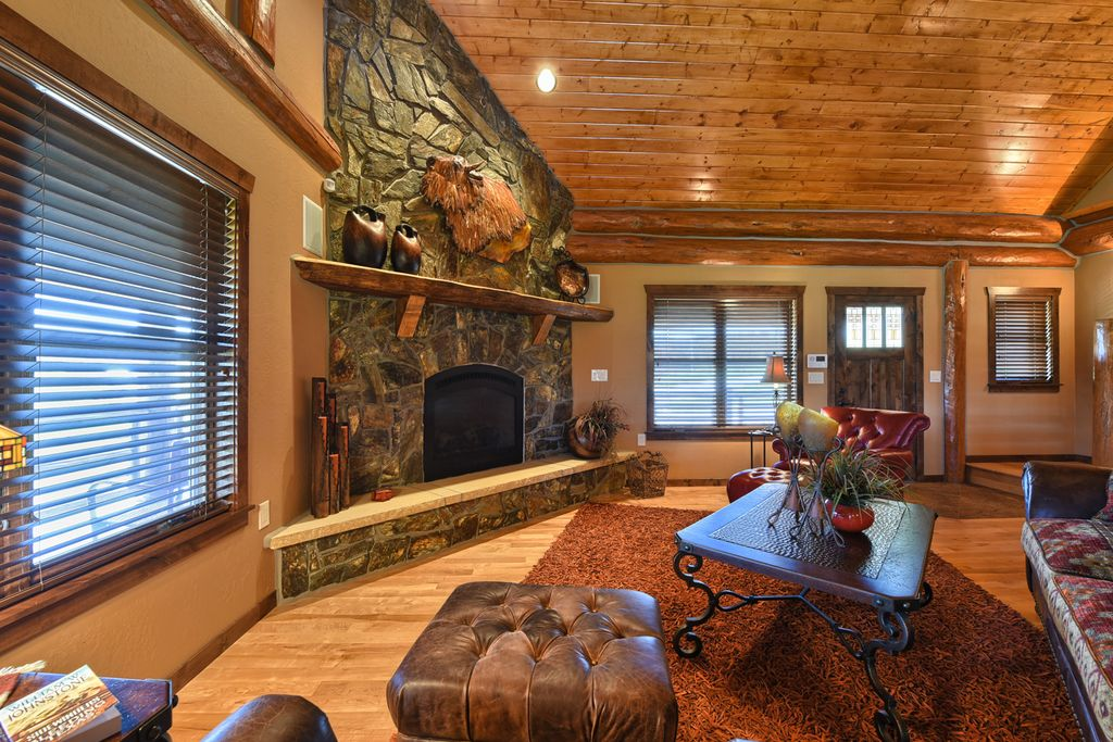 Rustic Living Room With Hardwood Floors & Stone Fireplace