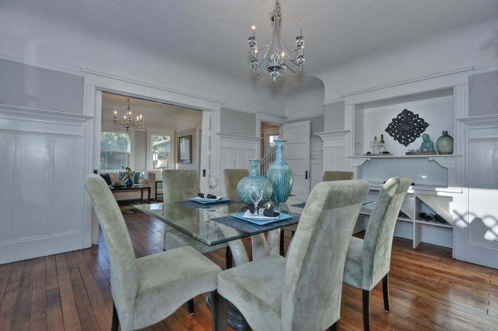 Transitional Dining Room With High Ceiling, Built In Bookshelf,  Wainscoting, Hardwood Floors