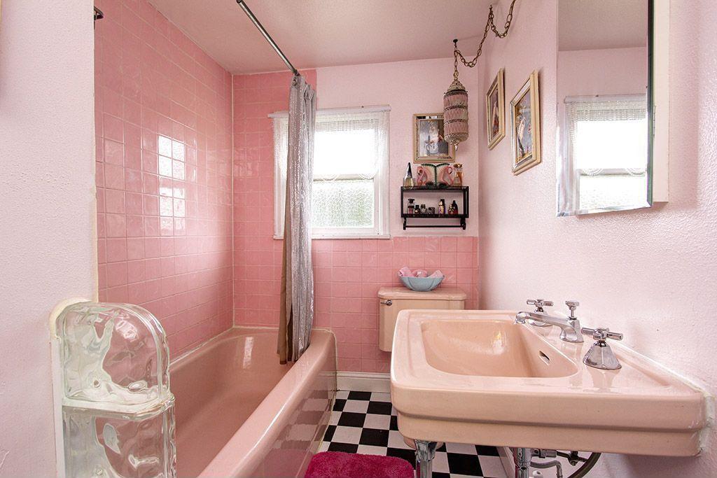 Pink pedestal sink in retro bathroom