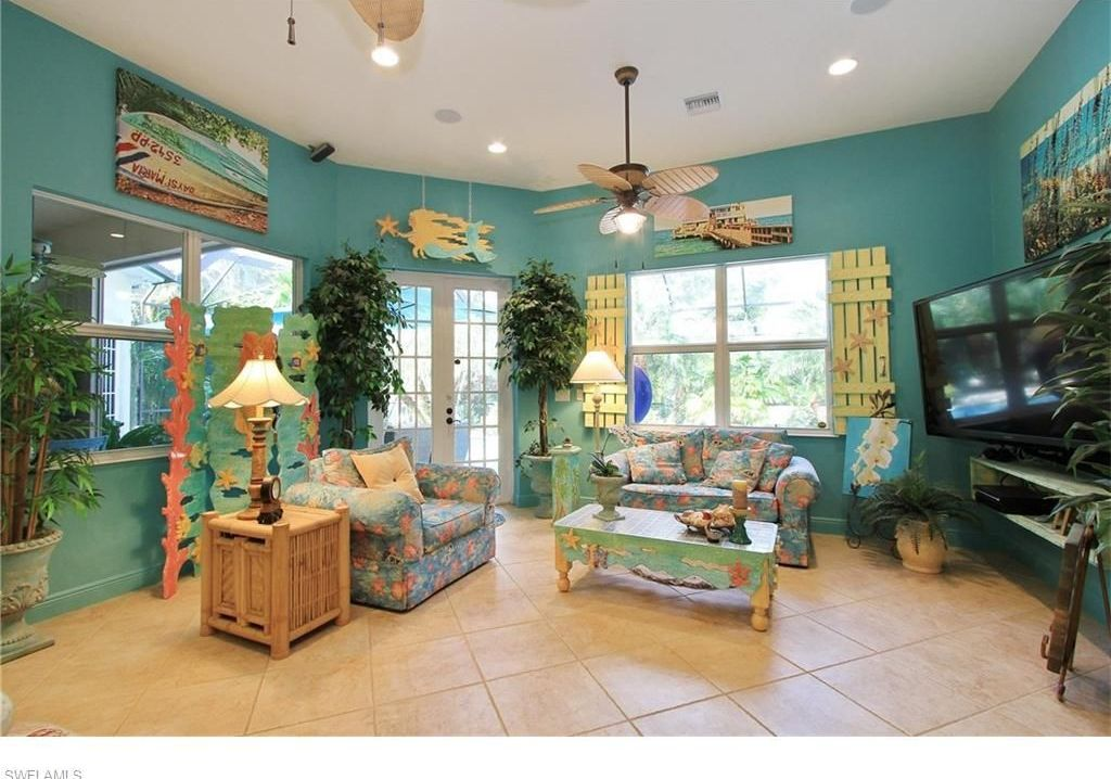 Tropical Living Room With High Ceiling, Limestone Tile Floors, Ceiling Fan,  Carpet,