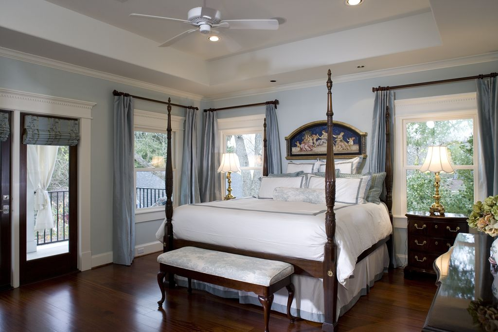 traditional master bedroom with ceiling fan high ceiling glass panel door hardwood floors