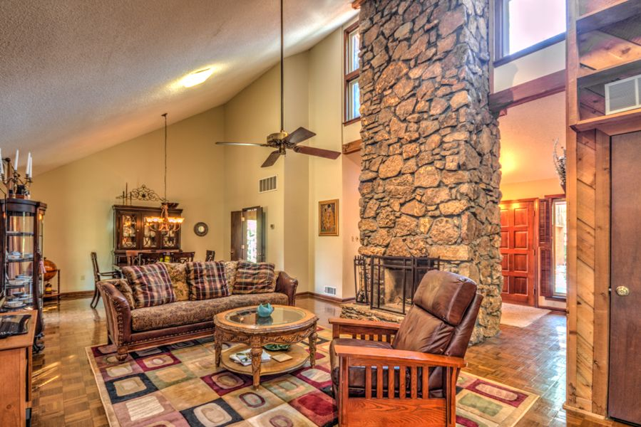 Rustic Living Room With Ceiling Fan Flush Light Laminate Floors Carpet Stone
