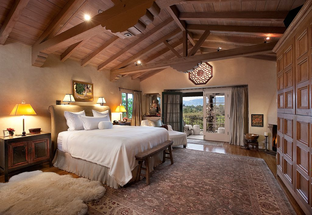 rustic master bedroom with cement fireplace french doors wall sconce