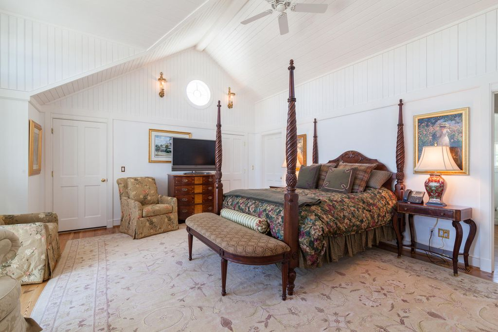 cottage master bedroom with exposed beam & ceiling fan in