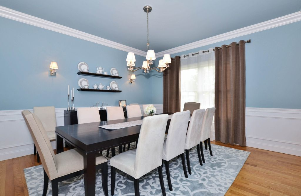 Traditional Dining Room With Wall Sconce Chandelier Crown Molding Wainscoting Carpet