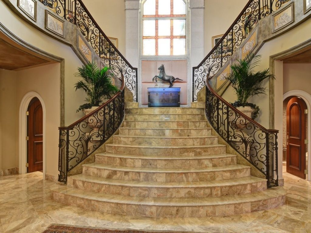Mediterranean staircase with travertine tile floors wainscoting mediterranean staircase with high ceiling wainscoting travertine tile floors arched window dailygadgetfo Image collections