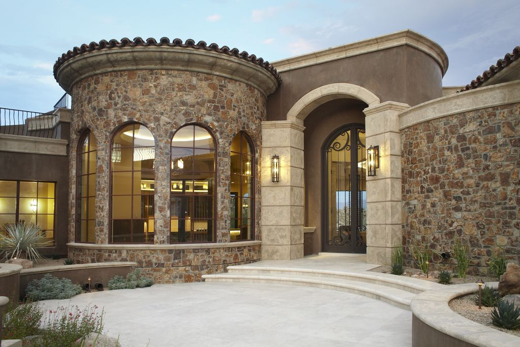 Mediterranean front door with exposed stone wall by for Mediterranean stone houses