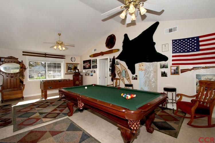 Eclectic Game Room With Travertine Tile Floors, Built In Bookshelf, Carpet,  Pool