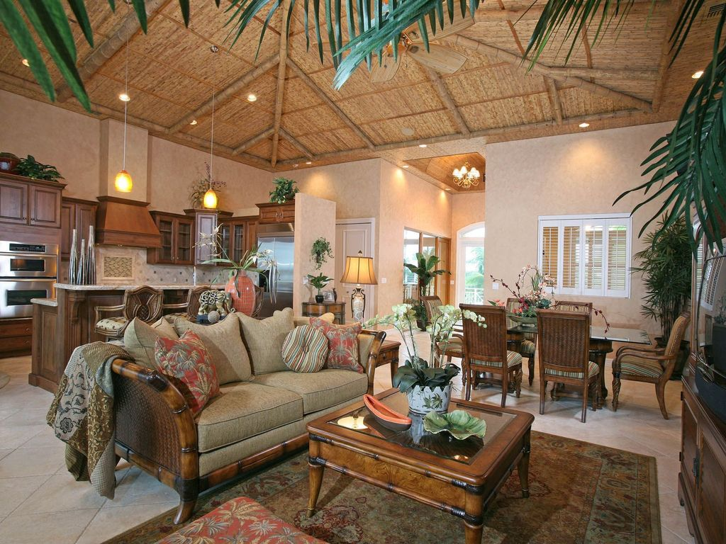 tropical great room with pendant light & travertine floors