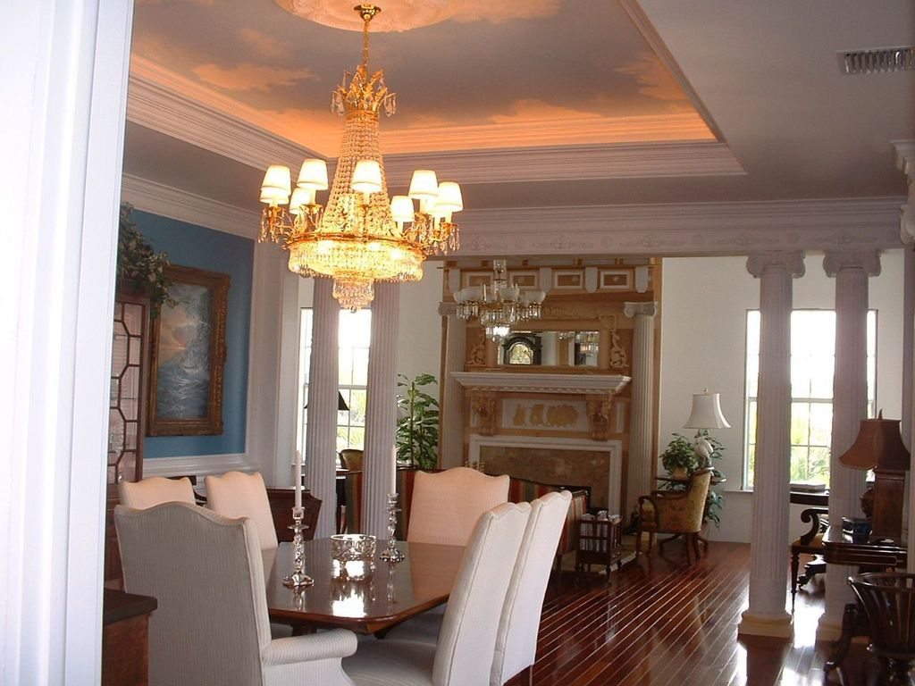 Traditional Dining Room With Columns, High Ceiling, Chandelier, Laminate  Floors, Crown Molding
